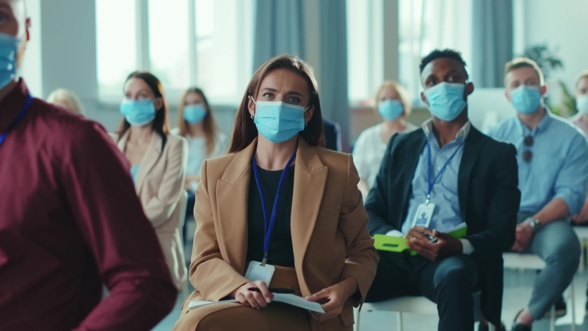 Diversity of corporate people in masks participating in conference meeting business seminar, raising hands to ask the speaker. Presentation. Social distance. Coronavirus. Royalty-Free Stock Footage #1056264173