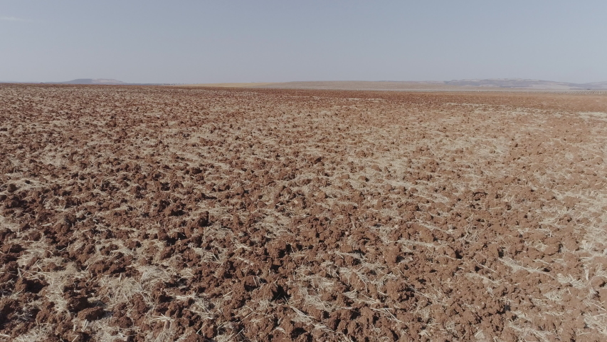 Aerial Drone fast close-up of dry plowed field and final upward movement with horizon and arid agricultural fields | Shutterstock HD Video #1056264845