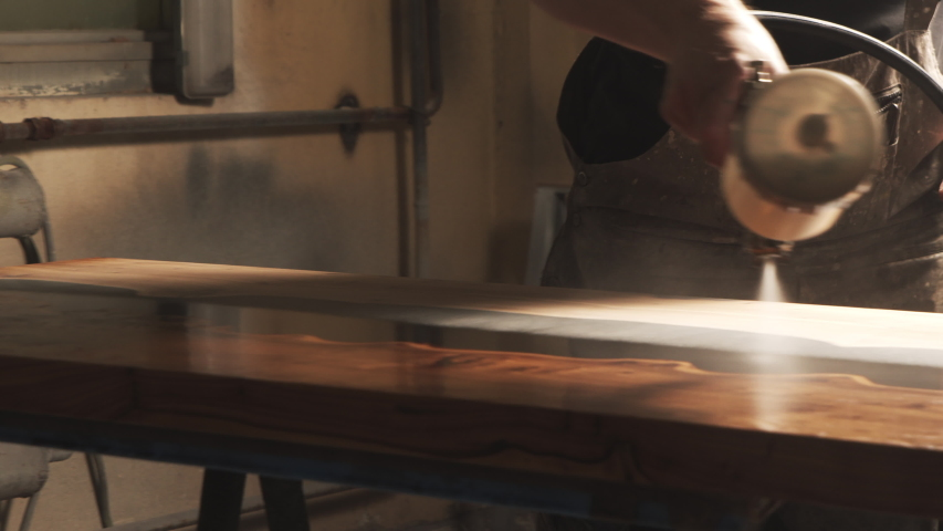 Close-up of a male carpenter's hands spraying varnish or primer using compressed air on a wooden tabletop. Furniture manufacture. Royalty-Free Stock Footage #1056265301