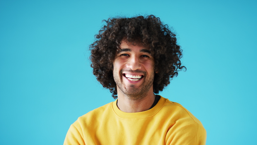 Studio portrait of confident smiling young man laughing against blue background - shot in slow motion | Shutterstock HD Video #1056266162