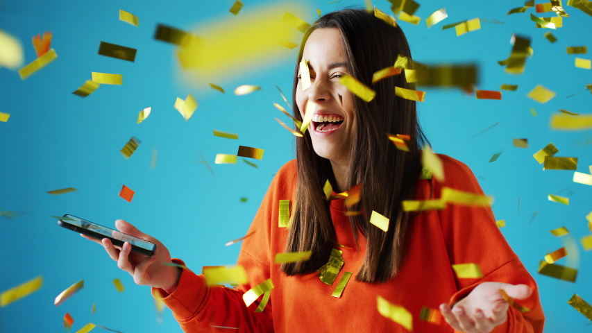 Celebrating young woman with mobile phone winning prize and showered with gold confetti in studio - shot in slow motion | Shutterstock HD Video #1056266165