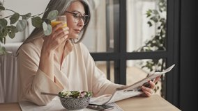 A gorgeous mature woman in eyeglasses is reading newspaper while eating breakfast sitting at the table at home