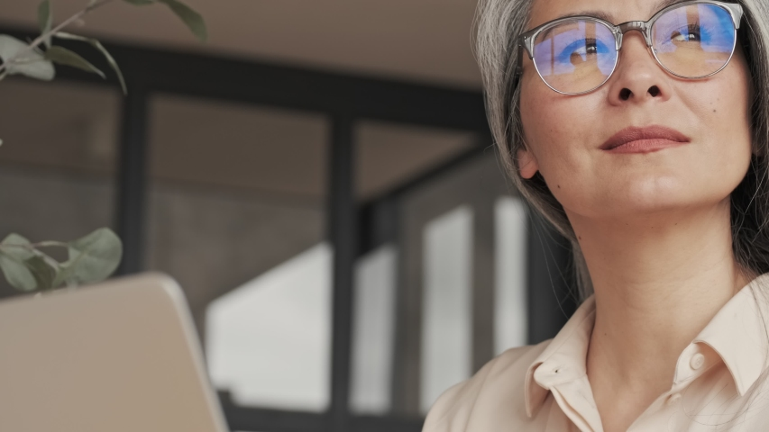 A close-up view of a thoughtful dreaming mature woman in eyeglasses is looking to her silver laptop computer sitting at home Royalty-Free Stock Footage #1056269477