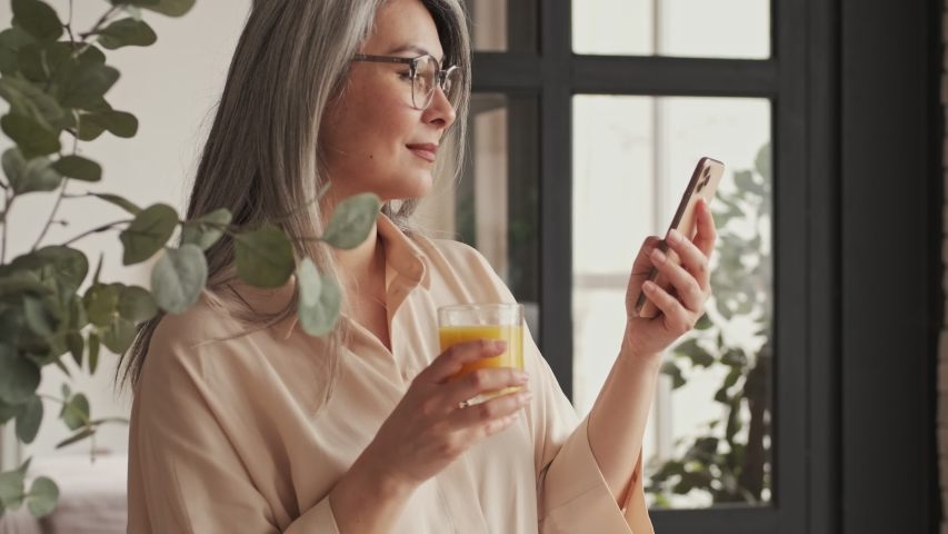 A side view of a good-looking mature woman in eyeglasses is drinking orange juice while watching something in her smartphone in the kitchen at home