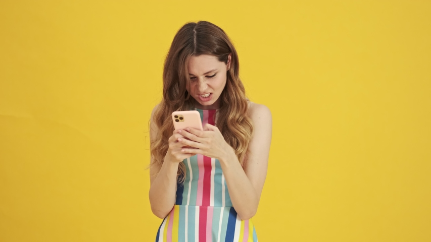 A displeased woman is writing message on her smartphone standing isolated over a yellow background | Shutterstock HD Video #1056269933