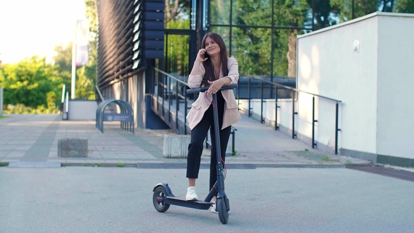 A young beautiful woman standing next to electric scooter while using her phone. She is smiling, business-dressed, with modern architecture in the background. | Shutterstock HD Video #1056272129