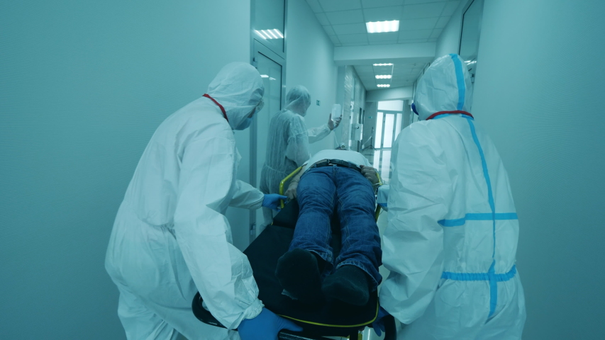 Coronavirus pandemic concept. Physicians in protective suits carry a man on stretcher. Royalty-Free Stock Footage #1056273290