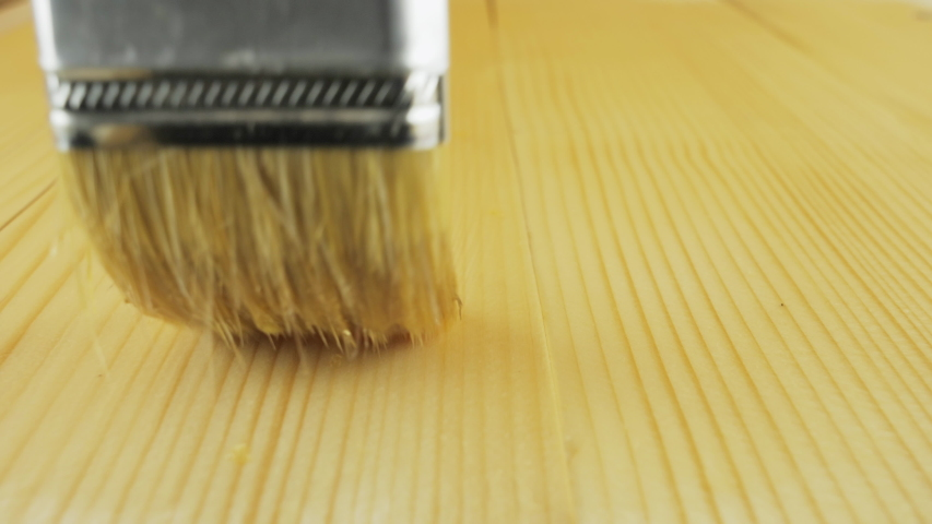 A person varnishes a wooden surface. Wood surface absorbs varnish. Painting wooden surface using a paintbrush. Paintbrush on wood table in close-up. Royalty-Free Stock Footage #1056273914
