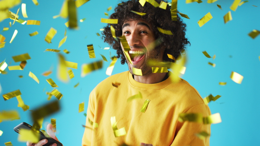 Celebrating young man with mobile phone winning prize and showered with gold confetti in studio - shot in slow motion | Shutterstock HD Video #1056277841