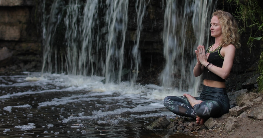 Blonde woman in sportswear practicing breathing yoga at the forest riverside near the waterfall. Fitness girl meditating with namaste mudra sign in harmony with nature. | Shutterstock HD Video #1056284390
