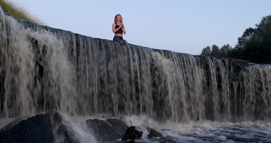 Fitness Girl in sportswear practicing yoga sitting on a top of waterfall at the sunset or sunrise time. Woman meditating with clasped hands in namaste mudra sign asana. Harmony with nature concept. | Shutterstock HD Video #1056284429