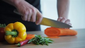 Close up shot of man hands slicing carrot on wooden cutting board. Man is cutting carrot into small pieces with sharp knife, healthy food, home cooking, diet, diet food, vegetarian food.