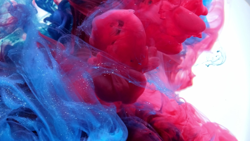 Blue and red mixing in water on white background, Slow motion.