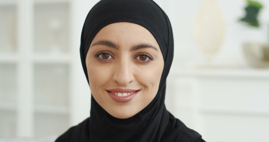 Portrait of beautiful young Arab muslim woman in black traditional hijab looking straight to camera and smiling. At home. Close up of female pretty face with smile. Arabian headscarf. Indoor.