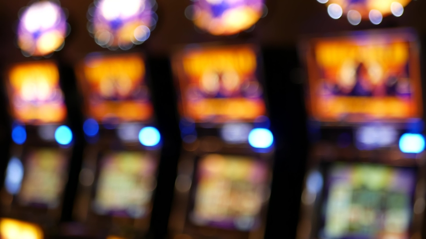 Defocused slot machines glow in casino on fabulous Las Vegas Strip, USA. Blurred gambling jackpot slots in hotel near Fremont street. Illuminated neon fruit machine for risk money playing and betting. | Shutterstock HD Video #1056289004