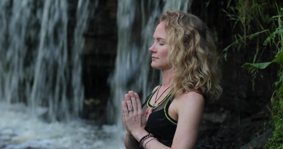 Close portrait of blonde woman in sportswear practicing breathing yoga at the forest riverside near the waterfall. Fitness girl meditating with namaste mudra sign in harmony with nature. | Shutterstock HD Video #1056289559