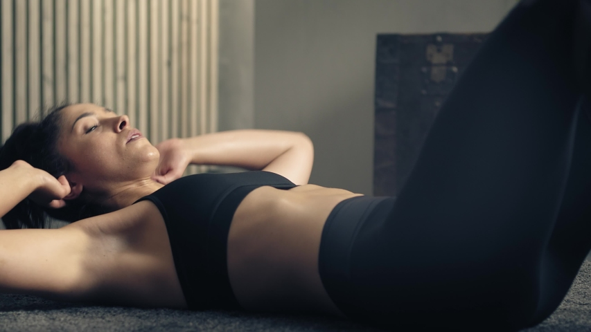 Detail of woman exercising on the floor at home.Woman doing cross crunch fitness training at home. Woman training abs. Industrial style house | Shutterstock HD Video #1056291410