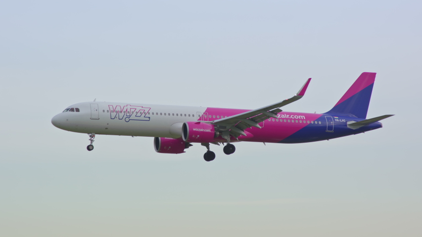 BARCELONA, SPAIN - 2020: Wizz Air Airbus A321neo Jet Airliner Early Morning Arrival Flying into Barcelona-El Prat BCN International Airport from a Vibrant Colorful Sky Landing and Touching Down
