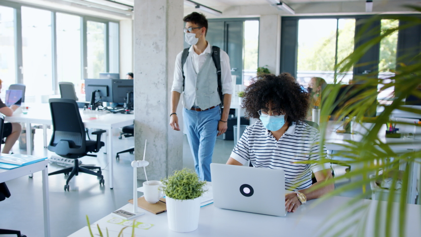 Young people with face masks back at work in office after lockdown, greeting. Royalty-Free Stock Footage #1056293702