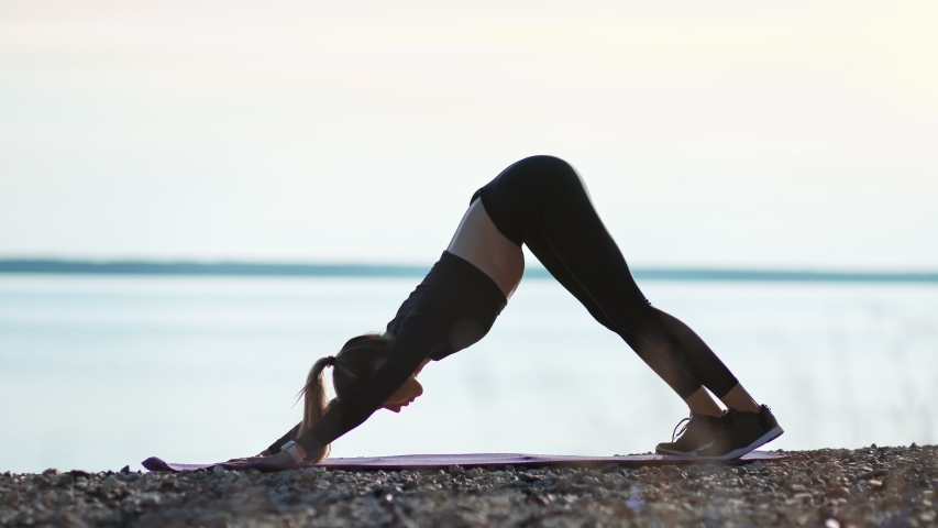Athletic young woman in earphones practicing upward downward dog yoga position at sunset beach. Fitness female training outdoor stretching body at morning nature. Shot on RED Raven 4k Cinema Camera Royalty-Free Stock Footage #1056295517
