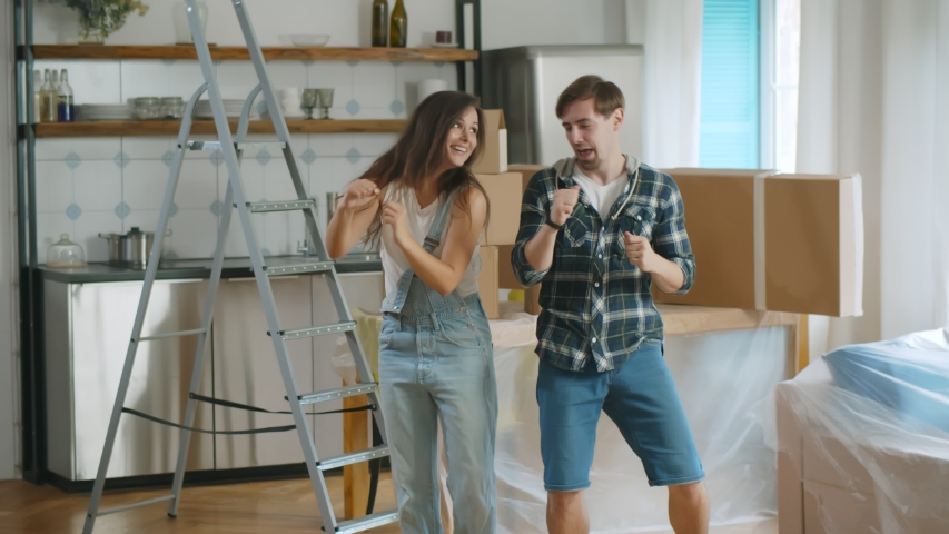 Young beautiful couple dancing at new home around cardboard boxes. Portrait of happy boyfriend and girlfriend having fun celebrating moving in new apartment together Royalty-Free Stock Footage #1056297122