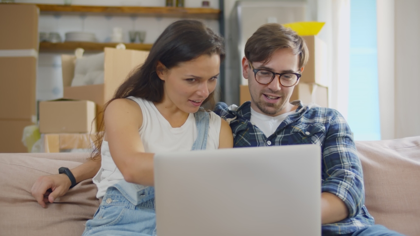Happy young couple using laptop choosing moving service. Man and woman moving in together relaxing on sofa couch with laptop buying decoration for new home online Royalty-Free Stock Footage #1056297128