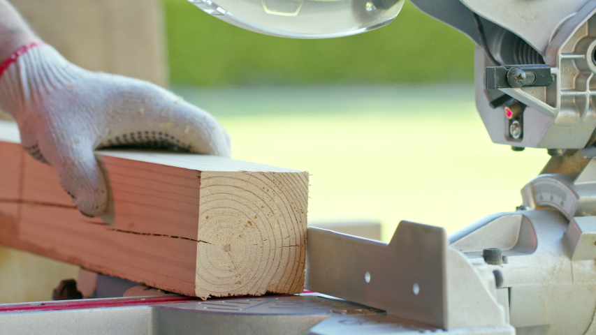 Woodworker in protective gloves precisely cuts off wooden workpiece on mitre saw close-up. cutoff piece falls nicely. Circular saw blade in motion, pine sawdust flying. DIY project concept | Shutterstock HD Video #1056297578