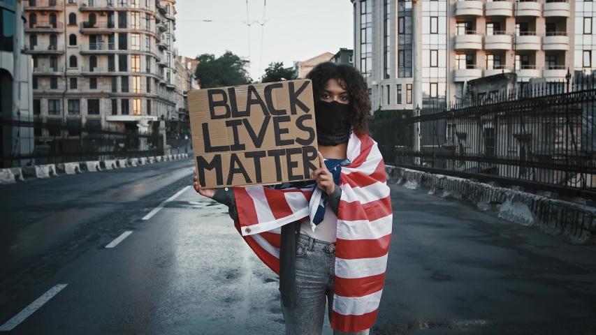 African-american protester in black bandana, wrapped in flag of USA. She showing cardboard tablet, inscription black lives matter. Standing on bridge