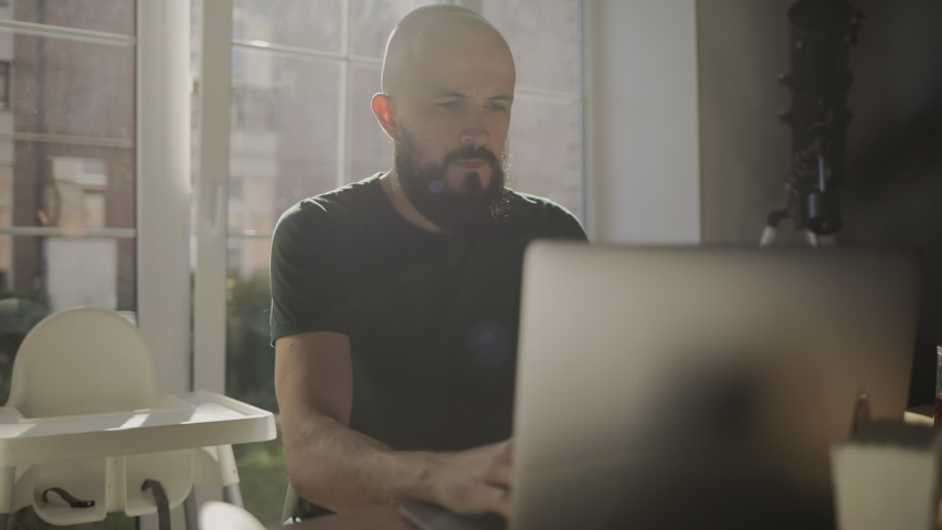 Freelancer programmer working from home on kitchen and using laptop. Bearded man working with a computer, prints text on keyboard. Self entrepreneur sitting and working at his modern apartment. | Shutterstock HD Video #1056300938