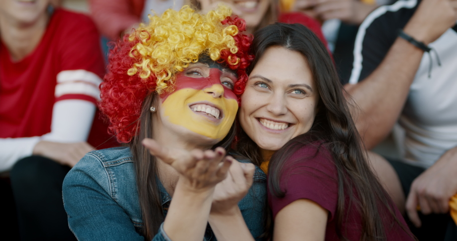Two women sitting in fan zone with a wig and face painted in german flag colors pointing at a big screen and blowing a kiss. Germany soccer team supporters looking themselves in a big screen at stadiu | Shutterstock HD Video #1056301862