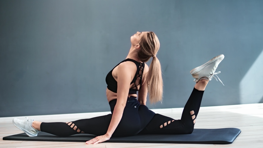 Athletic female sitting in twine on mat demonstrate flexibility at gym. Sportswoman lifting leg to head stretching body during pilates workout. Shot on RED Raven 4k Cinema Camera   Shutterstock HD Video #1056302810