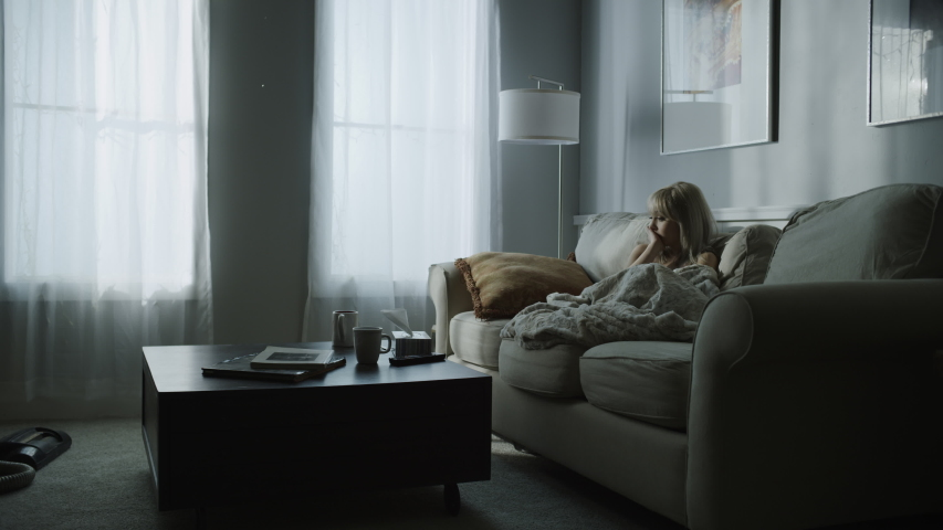 Distant woman sitting on sofa watching television / Cedar Hills, Utah, United States | Shutterstock HD Video #1056303719