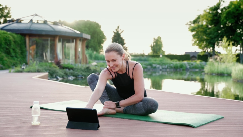 Teaching yoga online. Happy attracrive woman in sportswear looking at digital tablet and giving online yoga class while sitting on a mat in the park on a summer morning | Shutterstock HD Video #1056303779