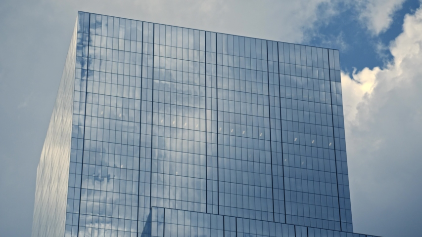 Downtown urban metropolitan top of tall blue office buildings reflecting cinematic clouds in summer timelapse