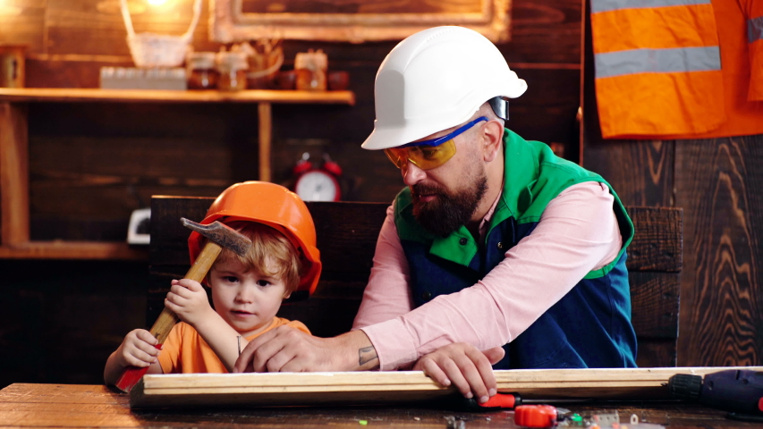 Father and little son with hammer hammering nail into wood plank at workshop. Family having fun, spending free time together, close up. Father teaching son | Shutterstock HD Video #1056314201
