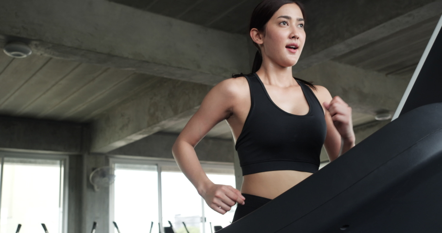 Athletic women running exercise at home during coronavirus outbreak. Asian girl running on treadmill. Woman healthcare while being quarantine at home.