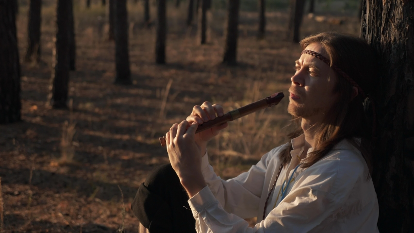 Close-up Man with Long Hair Plays Flute under Pine Trees. On Background Woman with Wreath and Basket Walks in Forest Nature. Slow motion 60 FPS Royalty-Free Stock Footage #1056320993