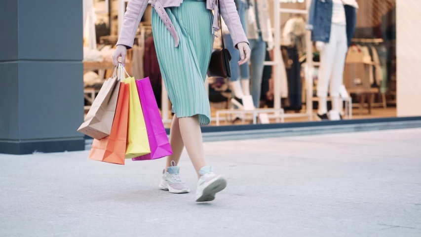 Young slim woman in skirt with shopping bags walking out from shopping center. | Shutterstock HD Video #1056329144
