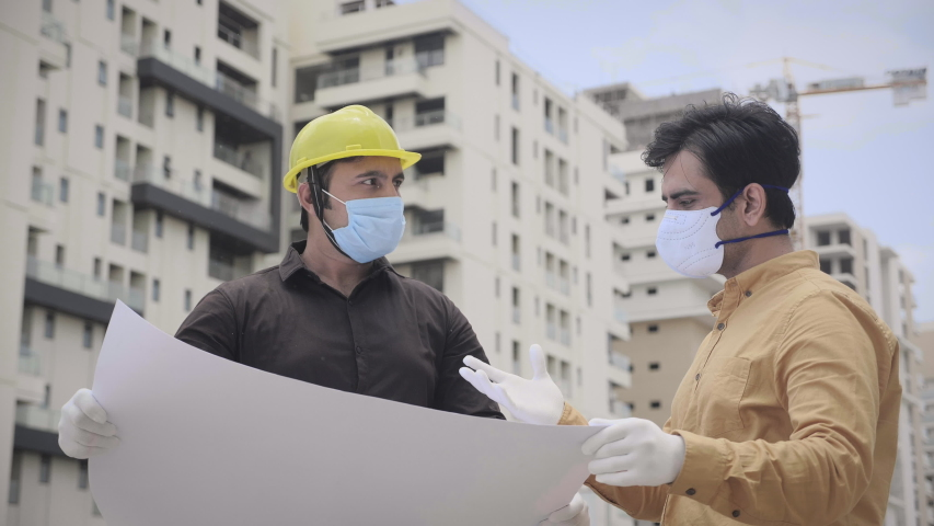 Two young male/ men engineers wearing face protective mask holding a blueprint of the building and working/ interacting outside under construction site amid Corona virus/ COVID 19 epidemic or pandemic