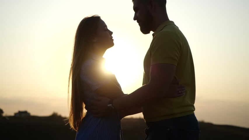 Silhouette of man and woman at sunset. Beautiful girl kisses guy in a deserted field, leaves and rises to hold her hands in slow motion. A romantic date and love on nature of loving happy couple Royalty-Free Stock Footage #1056340709