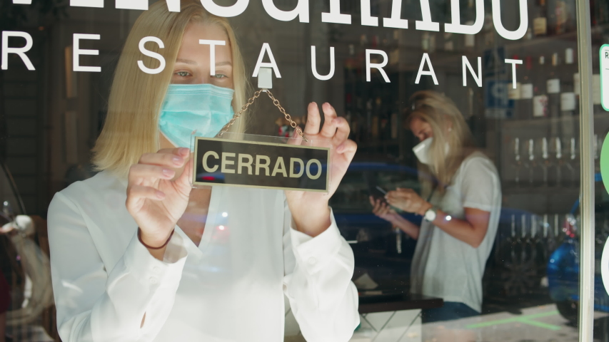 cafe or restaurants and business reopen after coronavirus quarantine is over. woman with face mask turning a sign on a door shop. small business after covid lockdown. Spain, barcelona Royalty-Free Stock Footage #1056340931