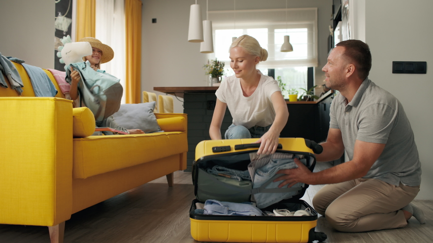 Happy family puts clothes in travel suitcase indoors of home room. Funny smiling girl takes things for summer vacation. Beautiful mom closes luggage before car tour or plane flight. Joy of family love