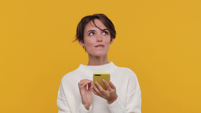 Smiling beautiful young woman girl 20s years old in white sweater posing isolated on yellow background in studio. People sincere emotions lifestyle concept. Look surprised hold using mobile cell phone