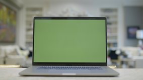 Home office. Green screen laptop computer sitting on a kitchen island. Footage shot with RED, available in 4K and HD. Download the preview for free.