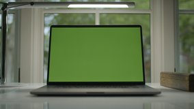Working from home. Green screen laptop computer sitting on a home work desk next to a desk lamp. Footage shot with RED, available in 4K and HD. Download the preview for free.