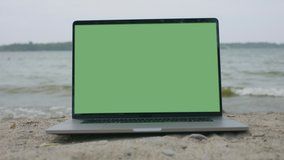 Working from the beach. Remote working new normal. Green screen laptop computer. Footage shot with RED, available in 4K and HD. Download the preview for free.