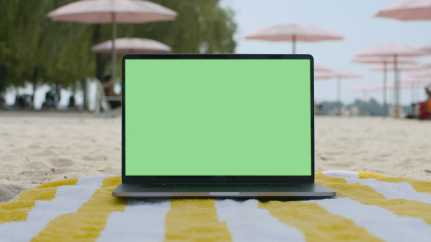 Remote work lifestyle. Working from the beach. Green screen laptop computer sitting on beach blanket.4K and HD. Download the preview for free.