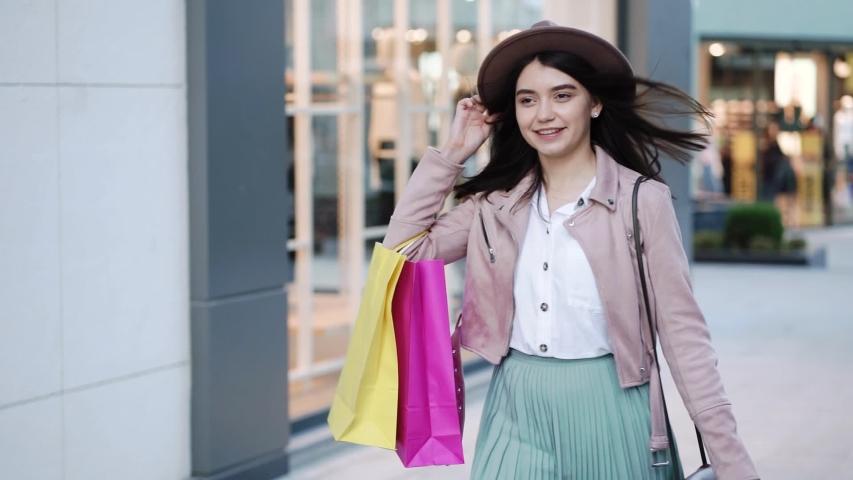 Young smiling woman in hat with paper bags walking in the shopping center after quarantine. | Shutterstock HD Video #1056356807
