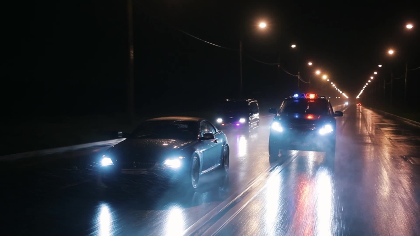 Cop cars are chasing an intruder's car in the rain. Outdoor front view of police traffic auto driving. Shot on the Russian Arm.