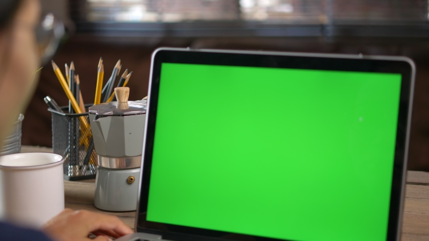 ​4K Dolly short. Over the shoulder shot of a business woman working in office interior on pc on desk, looking at green screen. Office person using laptop computer with laptop green screen, Royalty-Free Stock Footage #1056365339